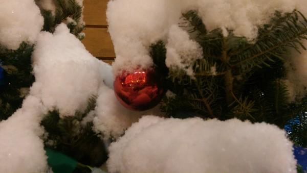 Ёлочный шарик на ёлке со снегом.